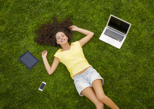 Beautiful and happy young woman lying on the grass surrounded by technology devices
